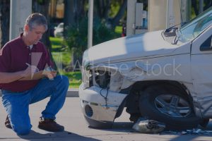 claims adjuster looking at damaged car